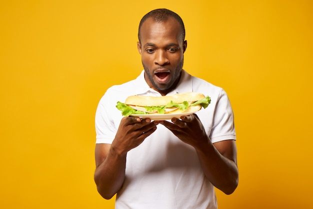 Homem negro animado detém grande sanduíche.