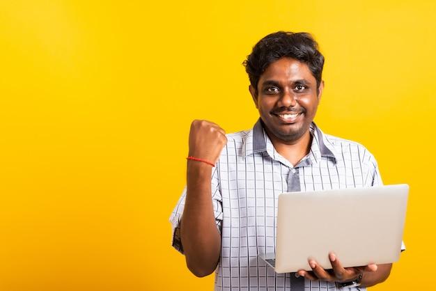 Homem negro animado segurando o computador portátil, cerrando os punhos e levantando a mão para o vencedor