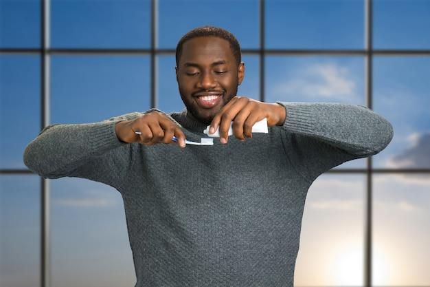 Homem negro aplicando pasta de dentes em uma escova de dentes. homem afro-americano sorridente com pasta de dente e escova