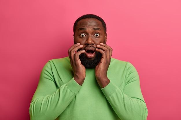 Homem negro assustado e assustado encara com olhos esbugalhados, testemunha o desastre, engasga com o choque, abre a boca amplamente, usa suéter verde