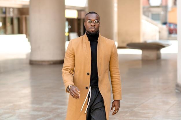 Homem negro atraente com cara séria, andando na cidade com pressa, vestindo roupas elegantes e elegantes.