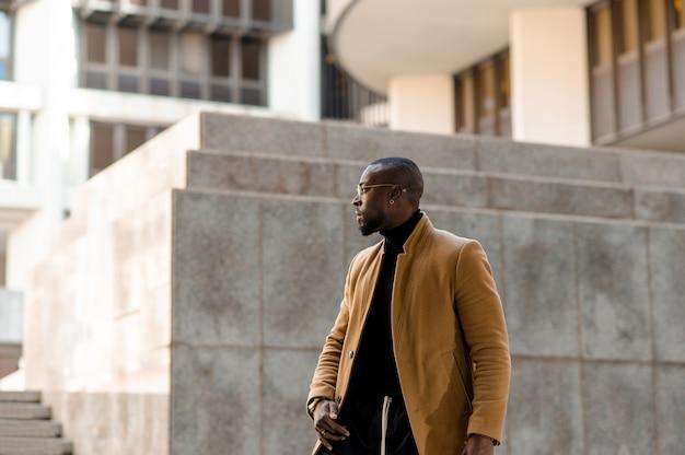 Homem negro atraente com roupas elegantes, caminhando em uma cidade metropolitana, olhando de lado.