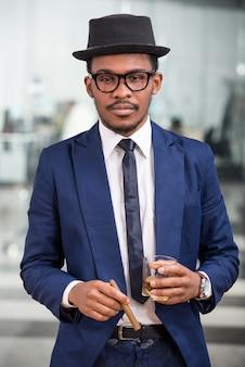 Homem negro atraente com um charuto e um copo de conhaque.