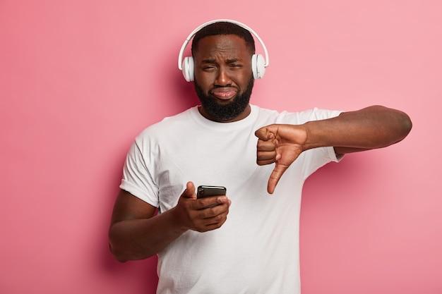 Homem negro barbudo insatisfeito demonstra gesto de desagrado, não gosta da música da playlist, ouve trilha sonora nos fones de ouvido