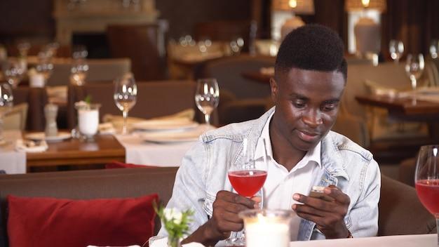 Homem negro bebendo vinho tinto no restaurante.