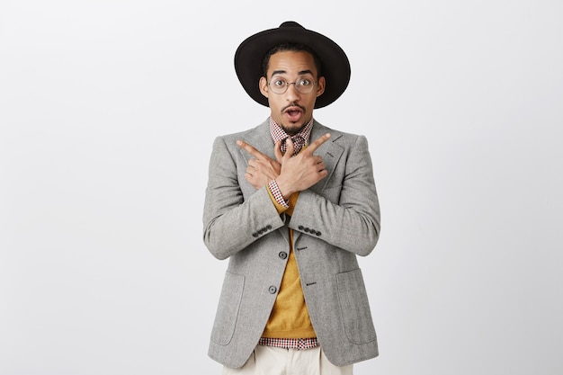 Homem negro bonito animado e impressionado apontando os dedos para o lado, mostrando duas opções