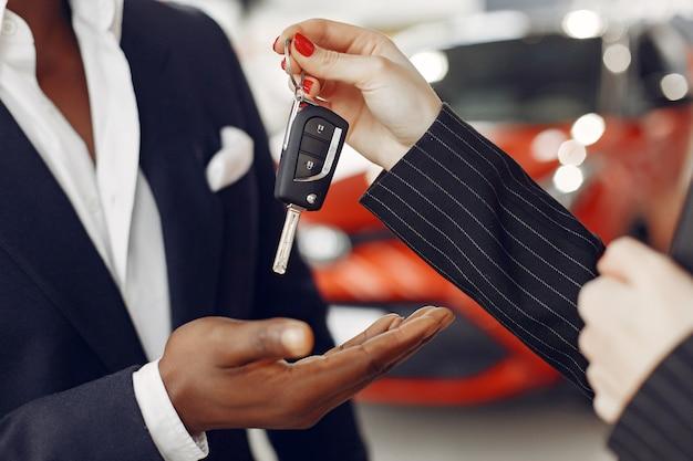 Homem negro bonito e elegante em um salão de carro