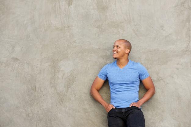 Homem negro bonito em t-shirt, sorrindo e olhando para longe