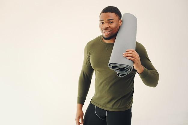 Homem negro bonito fazendo yoga em uma parede branca
