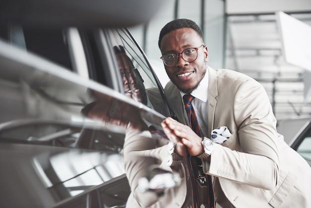 Homem negro bonito na concessionária está abraçando seu carro novo e sorrindo