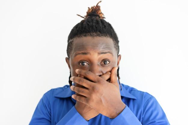 Homem negro chocado, cobrindo a boca com as duas mãos