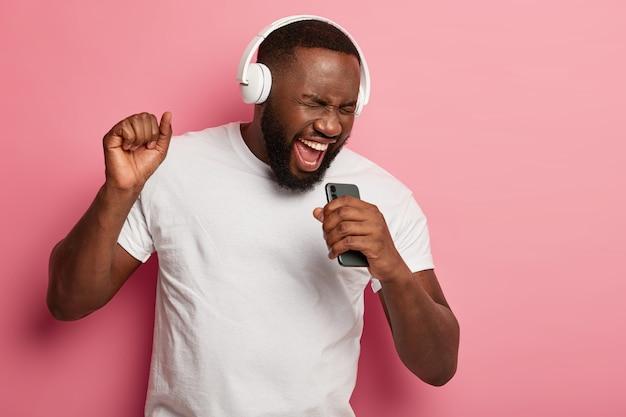 Homem negro com a barba por barbear energizado canta música, se move ativamente, usa fones de ouvido e camiseta casual, posa contra um fundo rosa, mantém a boca bem aberta