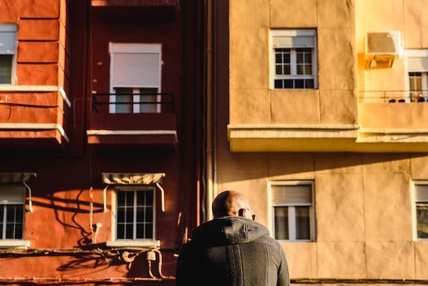Homem negro, com a cabeça raspada, de costas e sentado em frente a edifícios antigos