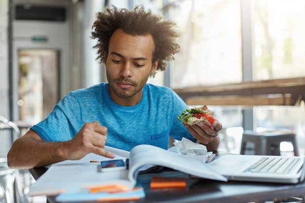 Homem negro com cabelo espesso olhando seu smartphone comendo sanduíche delicioso descansando
