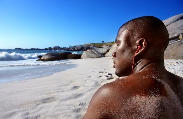 Homem negro com fones de ouvido na praia