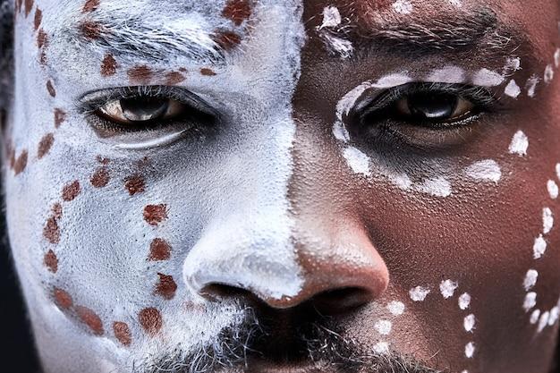 Homem negro com maquiagem étnica nacional no rosto, close de olhos pagãos