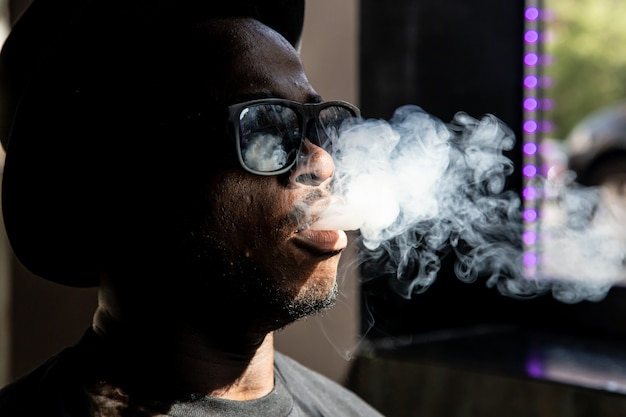 Homem negro com óculos de sol puxando fumaça da boca de um navio a vapor