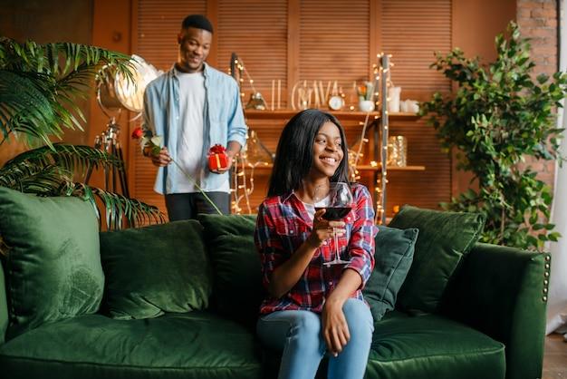 Homem negro com rosa vermelha e presente atrás de sua mulher com uma taça de vinho no sofá