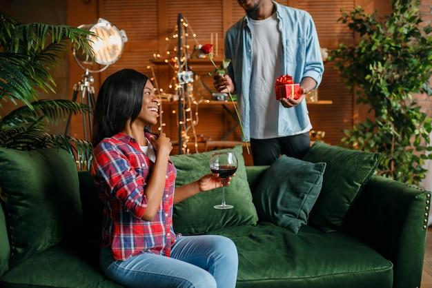 Homem negro com rosa vermelha e presente atrás de sua mulher