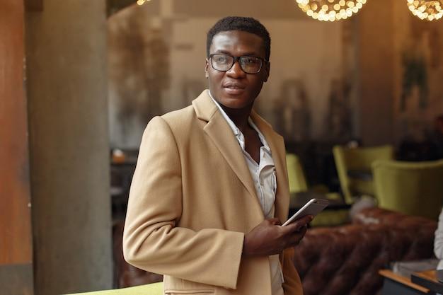 Homem negro com um casaco marrom de pé com o telemóvel