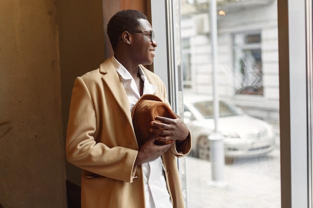 Homem negro com um casaco marrom em pé junto à janela