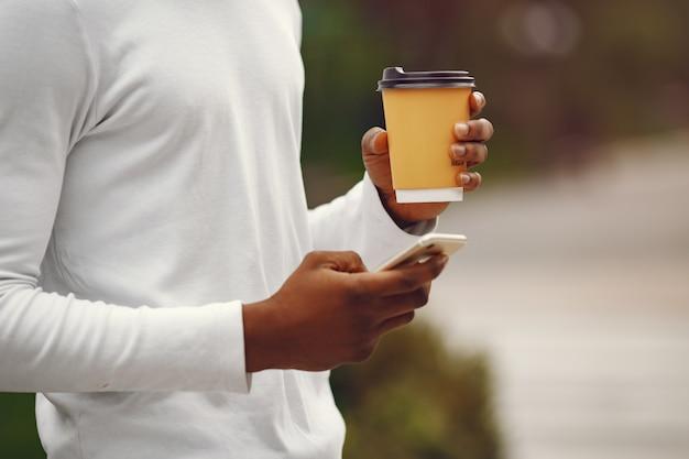 Homem negro com um suéter branco em uma cidade de verão