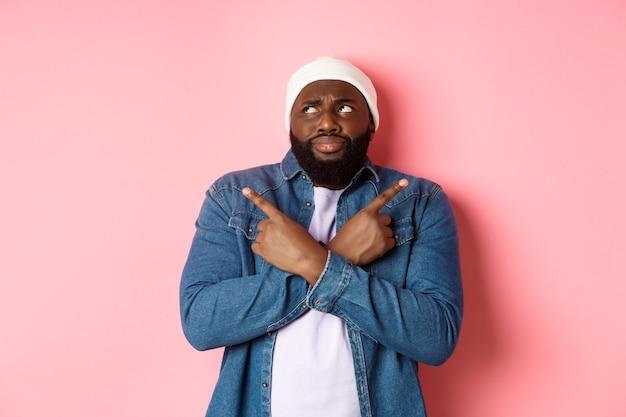 Homem negro confuso com barba, fazendo escolhas, apontando os dedos para os lados e parecendo perplexo, em pé sobre um fundo rosa.