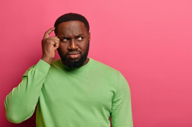 Homem negro confuso e inconsciente coça a cabeça, franze a testa enquanto olha para o lado, sente dúvida ou hesitação ao tomar uma decisão, usa um macacão verde, isolado na parede rosa do estúdio