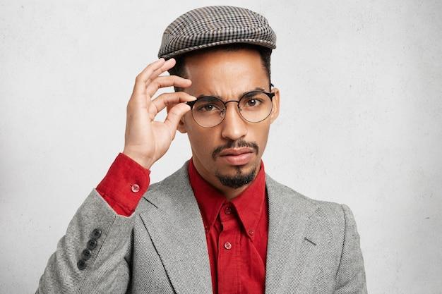 Homem negro convencido e autoconfiante usa óculos modernos, boné e jaqueta,