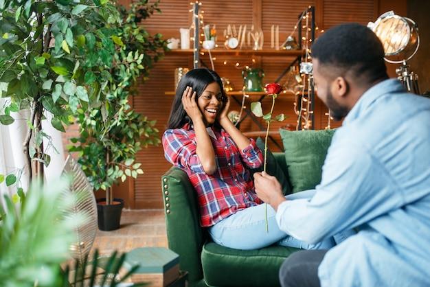 Homem negro dá rosa vermelha para sua mulher, encontro romântico em casa.