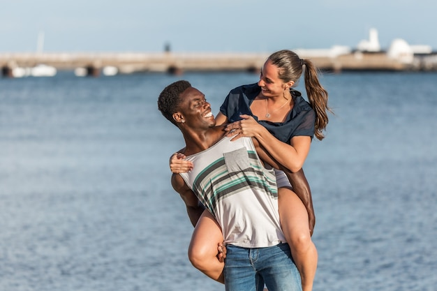 Homem negro dando carona para mulher perto do mar