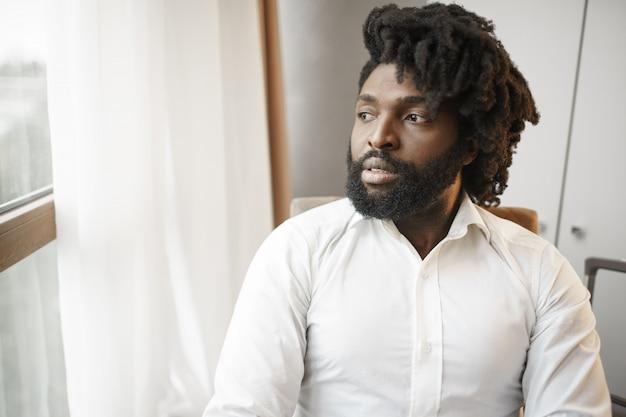 Homem negro de camisa formal, olhando pensativamente para a janela