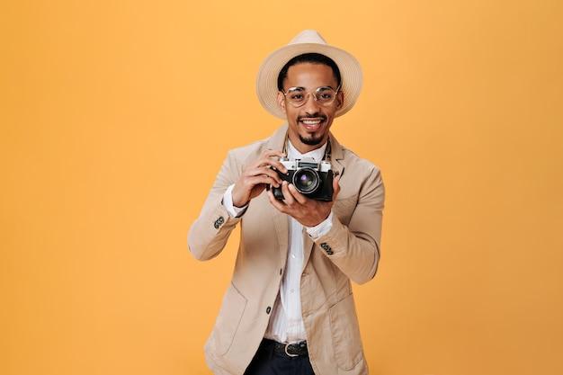 Homem negro de chapéu e óculos segurando uma câmera retro na parede isolada