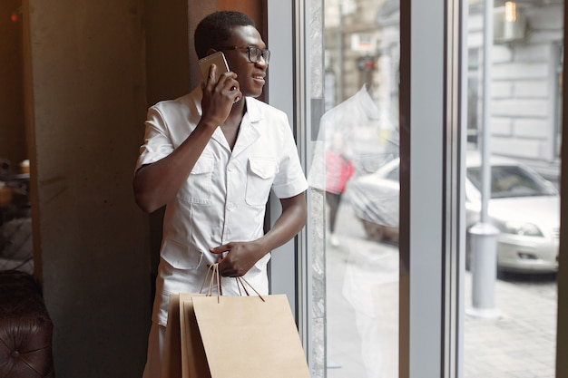 Homem negro de pé em um café com sacolas de compras
