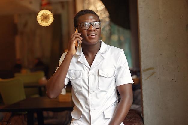 Homem negro de pé em um café e use o telefone