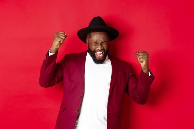 Homem negro de terno bem-sucedido dizendo sim, regozijando-se por ter vencido ou alcançado o objetivo, levantando as mãos e gritando de alegria, fundo vermelho