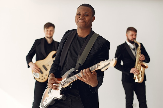 Homem negro de terno preto em pé com uma guitarra