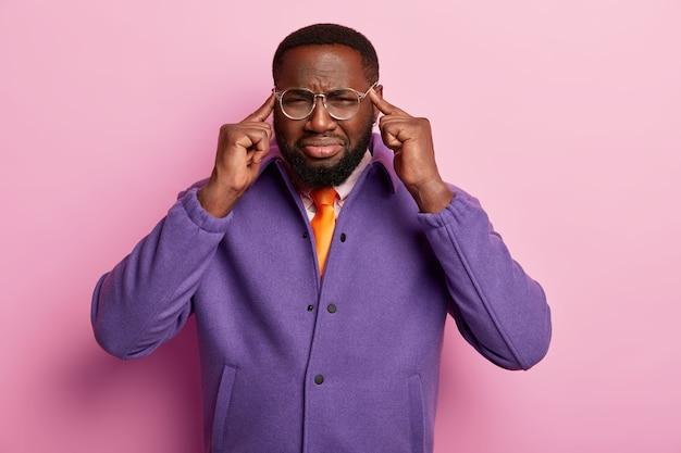 Homem negro descontente toca as têmporas com os dedos indicadores, sofre de enxaqueca, aperta o rosto e não consegue se concentrar por causa da dor de cabeça