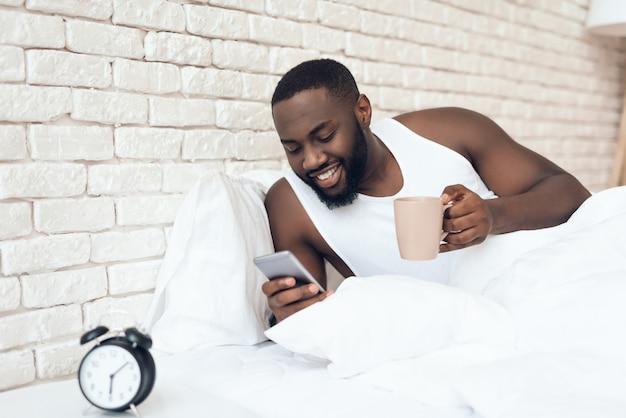 Homem negro e acordado bebe café na cama navegando na web.