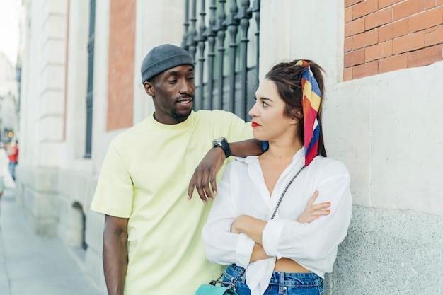 Homem negro e mulher caucasiana, olhando um ao outro. ela está de braços cruzados e ele está apoiado na menina. usar roupas casuais. parede no fundo