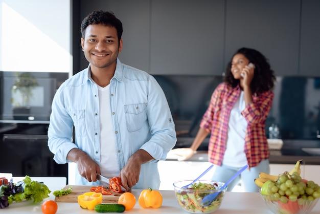 Homem negro e mulher estão preparando o café da manhã