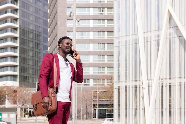Homem negro elegante com pasta falando ao telefone