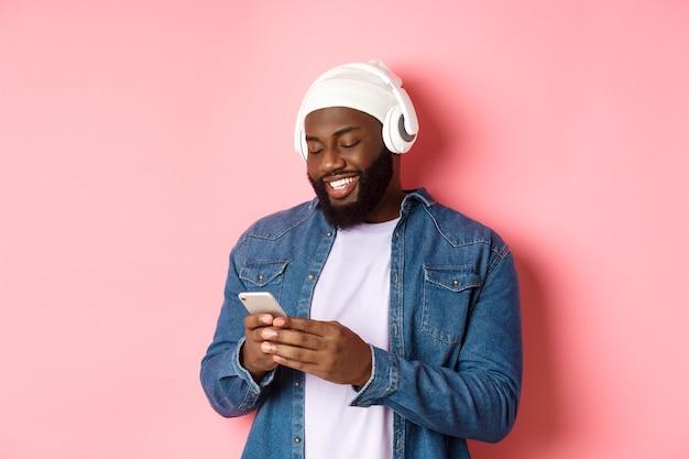 Homem negro elegante e bonito ouvindo música em fones de ouvido e escrevendo mensagens no smartphone, sorrindo feliz, em pé sobre um fundo rosa