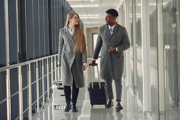 Homem negro elegante no aeroporto com seu parceiro de negócios