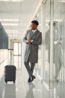 Homem negro elegante no aeroporto com uma mala