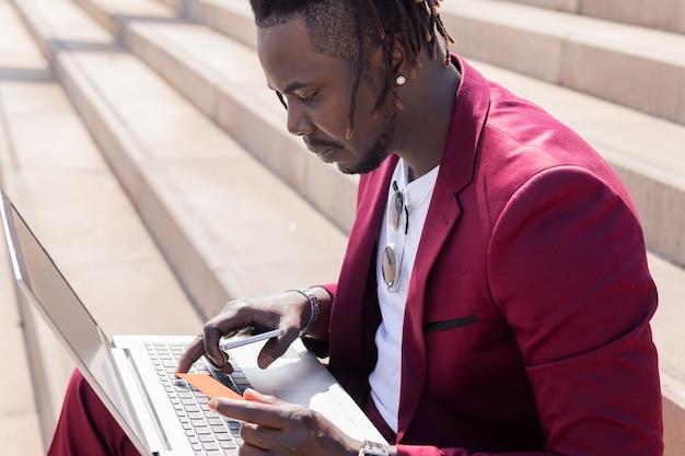 Homem negro elegante sentado ao ar livre paga com seu cartão de crédito a compra online feita em seu laptop, tecnologia e conceito de compra online