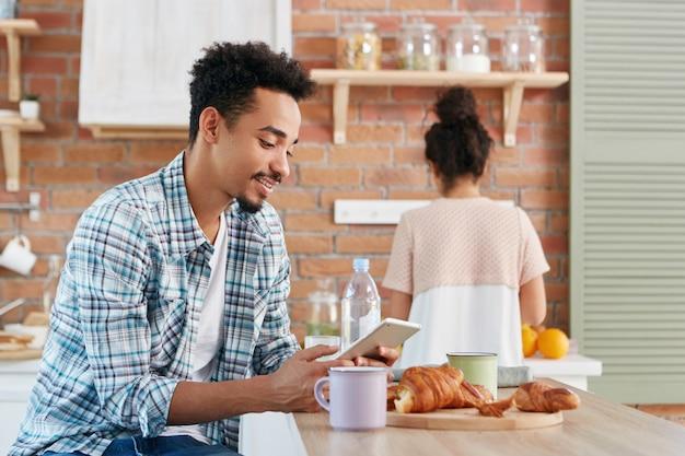 Homem negro em roupa casual verifica e-mails ou lê notícias mundiais em dispositivos eletrônicos, bebe café pela manhã e croissants