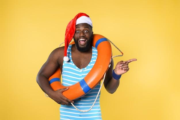 Homem negro em traje de banho pronto para ir em um lugar ensolarado para o natal. parede amarela
