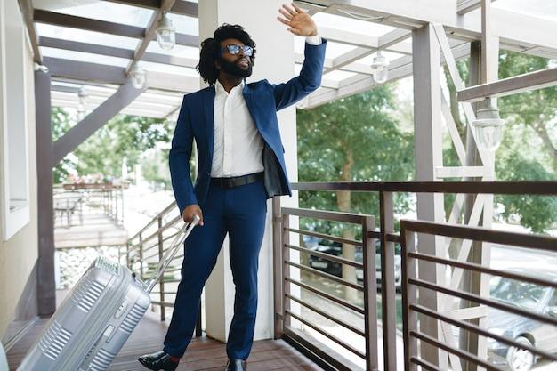 Homem negro em um terno formal com mala feita, entrando na porta do hotel.