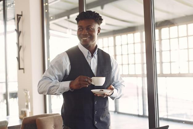 Homem negro em uma camisa azul em pé em um café